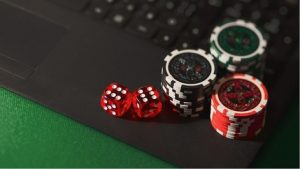 Dice and casino chips on a laptop